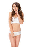 Young slim brunette girl posing in a studio in lacy underwear Royalty Free Stock Image