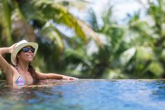 Young slim brunette woman sunbathe in tropical swimming pool stock photography