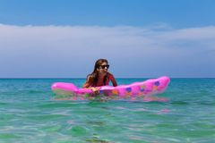 Young slim brunette woman in sunglasses swimming on an air mattress on a tropic beach stock photo