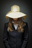 Young slim Caucasian business woman studio shot on gray background. Wearing a straw sun hat Royalty Free Stock Photo