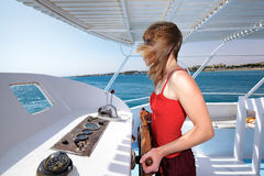 Young slim Caucasian woman in red sundress and sunglasses standing on old ship deck at the steering wheel and looking at sea Royalty Free Stock Photos
