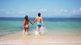 Young slim couple holding hands running into tropical sea on sunny day. slow motion. 1920x1080. Young slim couple hold hands running into tropical sea on sunny stock video footage