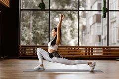 Young slim dark-haired girl dressed in white sports top and tights is doing reverse lunge and reach arms high in the gym stock photo