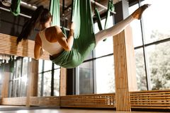 Young slim dark-haired girl dressed in white sports top and tights is doing yoga on green hammock stock image