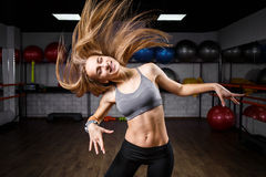 Young slim fitness girl with long waved hair. In health club. Smiling caucasian girl in fitness center Stock Photography
