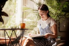 A young slim friendly girl with dark hair,dressed in casual outfit,sits at the table and reads a book in a cozy coffee royalty free stock photography