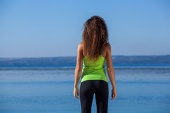 Young slim girl in black and light green sports suit sitting after jogging walks on the beach. Stock Images