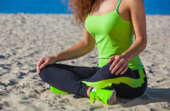 Young slim girl in black and light green tracksuit sitting after a workout in the sand on the seashore. Stock Images