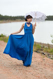 Young slim girl in a blue dress with an umbrella Stock Photography