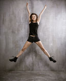 Young slim girl in boots, shorts and a vest, jumping on a backgr Royalty Free Stock Photo