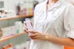 A young slim girl,dressed in a white coat, is holding a spray in her hands in a new pharmacy. royalty free stock photo