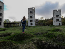 A young Slim girl with long blond hair stands on a vacant lot in front of three dilapidated towers on a cloudy day. She stands with her back on the hill and Royalty Free Stock Photo