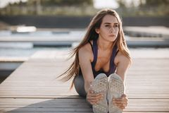 Young slim girl with long brown hair in a sports top and tights doing stretching on the wooden pier royalty free stock photo