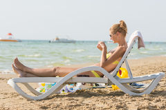Young slim girl lying on sun lounger on the beach and makes nail polish Royalty Free Stock Photography