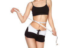 Young slim girl measuring waist tape. Royalty Free Stock Photo