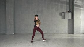 Young slim girl performing contemporary dance in studio. Athletic girl practicing modern dance moves. Art of street dance stock video
