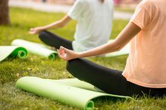 Young slim girl sits relaxing in the lotus position doing exercises on yoga mats with other girls on green grass in the stock photography