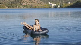 Young slim girl floats on inflatable mattress stock footage