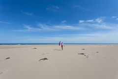 Young slim girl standing on the wide sandy beach and waves hand on the background of blue sky. Royalty Free Stock Images