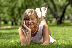Young slim girl in a summer dress lying on the grass in the meadow with flowers Stock Photos