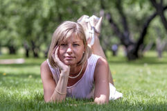 Young slim girl in a summer dress lying on the grass in the meadow with flowers Royalty Free Stock Photography