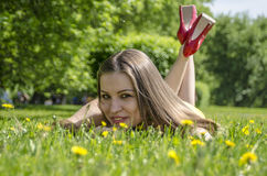 Young slim girl in a summer dress lying on the grass in the meadow with flowers Royalty Free Stock Image