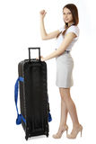 A young, slim girl teenager 16 years old, stands next to a huge, black suitcase on wheels. Teen girl hitchhiking. Stock Image