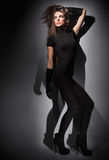 Young slim glamour lady dressed in black. Young slim glamour lady with long hairs dressed in black combi dress, dark key studio portrait Stock Photos