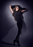 Young slim glamour lady with long hairs. Dressed in black combi dress, dark key studio portrait Stock Photos