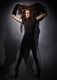 Young slim glamour lady with long hairs on black Royalty Free Stock Photos