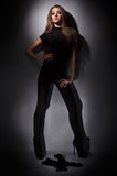 Young slim glamour lady with long hairs in black. Young slim glamour lady with long hairs dressed in black combi dress, dark key studio portrait Stock Photography
