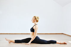 Young slim gymnast woman in sports clothing stretching indoors Royalty Free Stock Photography