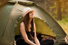Young slim hiker woman sitting at small tourist tent enjoying beautiful nature forest on bright summer morning. stock image