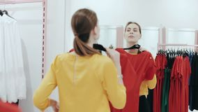 Young slim lady with ponytail choosing a dress in clothes shop. Woman shopping and checking clothes in front of mirror. Young slim lady with ponytale choosing a stock footage
