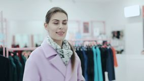 Young slim lady with ponytale trying on a coat. Woman shopping and checking pink coat in front of mirror. Style and. Young slim lady with ponytale trying on a stock footage