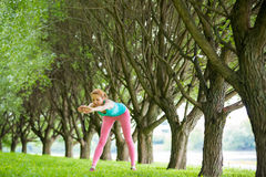 Young slim lady training in the park Royalty Free Stock Photos