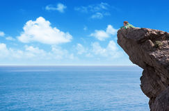 Young slim lonely woman laying at the edge of mountain cliff abo Royalty Free Stock Image