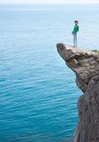 Young slim lonely woman standing at the edge of mountain cliff stock photography