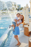 Young slim mother in a blue skirt holding her son hands and laughing, against the background of the hotel in summer stock images