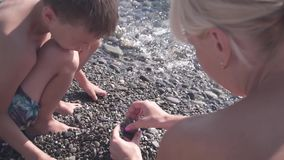 Young slim mother and her son play with pebbles on beach, slow motion stock video