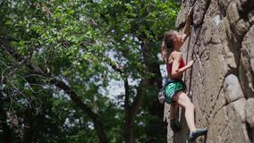 Young slim muscular woman rockclimber climbing on tough sport route, reaching and gripping hold and clipping rope to