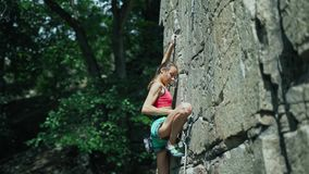 Young slim muscular woman rockclimber climbing on tough sport route, reaching and gripping holds and trying to attach