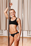 Young slim pole dance blond woman holding pole and smile Royalty Free Stock Photos