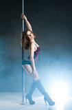 Young slim pole dance woman exercising over dark Stock Photography