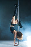 Young slim pole dance woman exercising over dark Royalty Free Stock Image