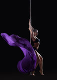 Young slim pole dancer posing with violet cloth Stock Images