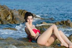 Young slim pretty lady wear bikini lying on sea rocks royalty free stock photography