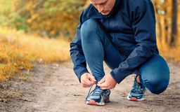 Young slim runner in a black sports leggins and sneakers ties la royalty free stock photos