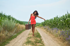 Young slim sexi tanned lady in red short dress. Portrait of sexi tanned girl in red short dress carrying retro suicase walking barefoot along earth road in field Stock Images