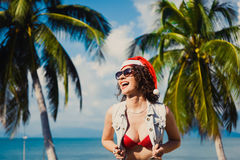 Young slim sexy girl red hat of Santa Claus on Christmas smartphone. Closeup of a young slim    sexy girl in sunglasses red hat of Santa Claus on Christmas in Stock Photography